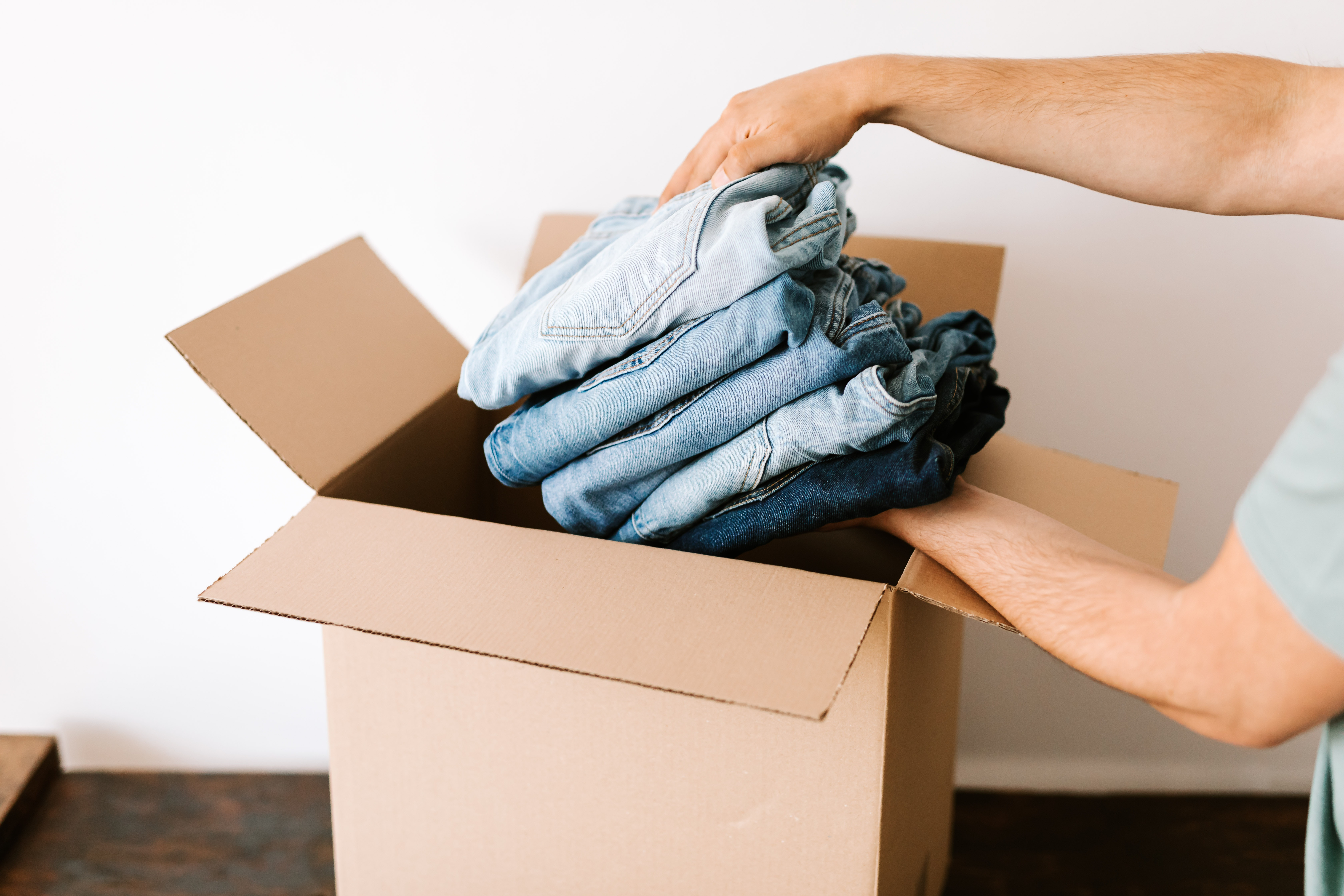 person packing jeans into a box