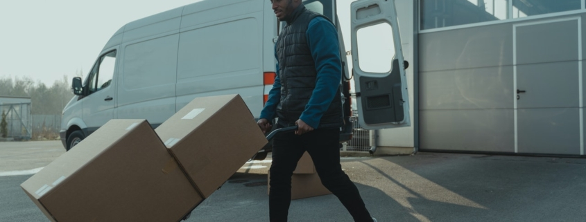 Guy moving boxes on a dolly